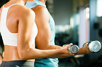 a man and a woman, both very fit, exercise with dumbbells