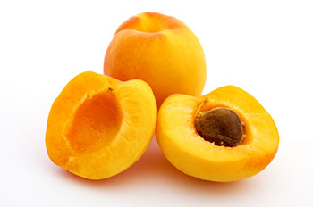 2 apricots - one is sliced in half to show the pit