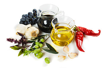 a carafe of balsamic vinegar and a carafe of olive oil, flanked by garlic, fresh green olives, and red peppers