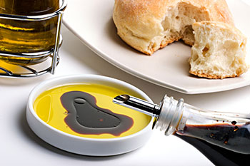 Balsamic vinegar being poured into a dish already containing olive oil. Bread is nearby for dipping.