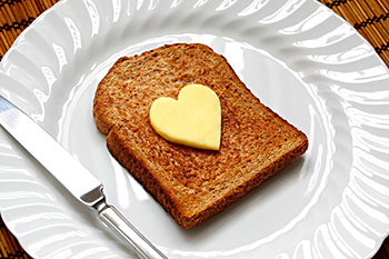 a slice of wheat toast topped with a pat of butter in the shape of a heart