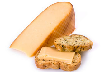 A larger wedge of gouda cheese and a small portion served on a crouton