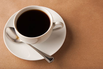 A cup of black coffee on a saucer with a spoon