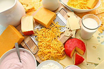 an array of cheeses and other dairy products, including yogurt and milk