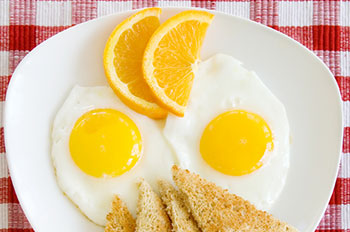 a breakfast meal of fried eggs and toast garnished with a slice of orange