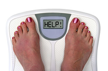 top view of two bare feet standing on a personal scale that reads 'HELP' instead of a number