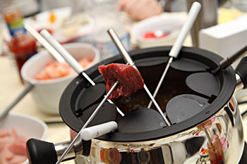 A fondue pot filled with oil - a cube of meat is held on a fondue fork, ready for dipping
