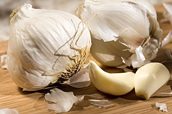 two heads of fresh garlic flanked by two garlic cloves