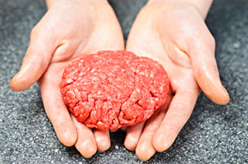 an uncooked ground beef patty held in a person's hands