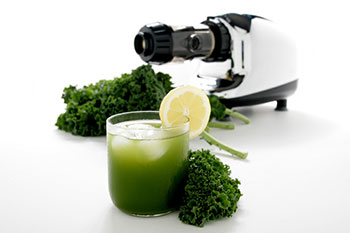 A glass of kale juice with fresh kale and a juicer in the background