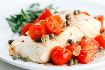 A piece of roasted halibut topped with cherry tomatoes, sliced garlic, and capers