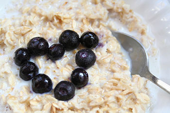 a bowl of steel-cut oatmeal garnished with blueberries arranged in a heart