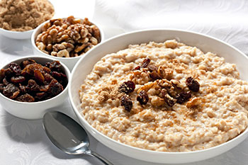 a bowl of cooked oatmeal garnished with brown sugar, nuts, and raisins