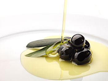 olive oil being drizzled over a spray of olive leaves and black olives