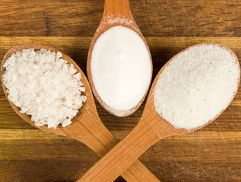 Three wooden spoons holding three different levels of salt: coarse, medium, and fine (or table salt)