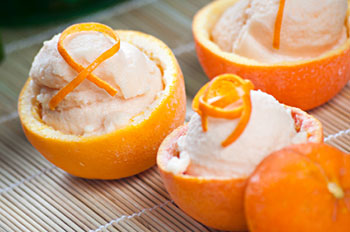 Scoops of lactose-free orange sorbet served in hollowed-out oranges