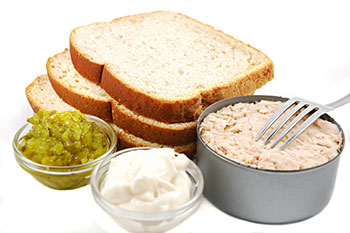 The makings of a tuna sandwich: canned tuna, bread, pickle relish, and mayonnaise
