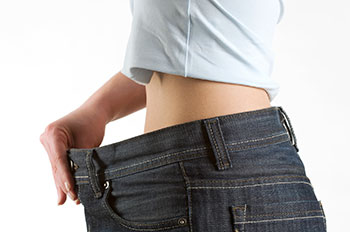 Person holding the waistband of an oversize pair of pants away from their waist