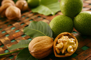 several whole walnuts on a woven mat with one walnut split open to show the nut meat