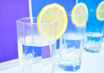 a clear water glass filled with water and garnished with a slice of lemon
