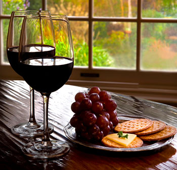 two wineglasses containing red wine next to a plate of grapes, cheese, and crackers