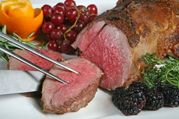 a beef tenderloin being sliced with a knife and fork, with grapes and blackberries for garnish