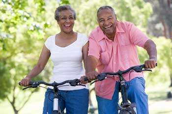 two African-American adults, both smiling, enjoying a bicycle ride