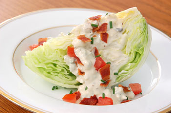 a wedge of iceberg lettuce topped with blue cheese dressing and bacon bits