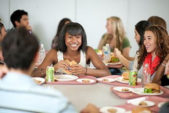 a group of adolescents having lunch together around a table in a school lunchroom