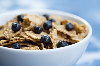 a bowl of breakfast cereal garnished with blueberries