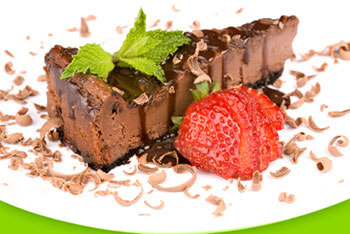a slice of chocolate cheesecake garnished with curls of chocolate and a sliced strawberry