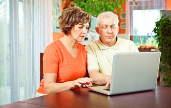 two older persons sitting together at a table looking at a laptop computer screen