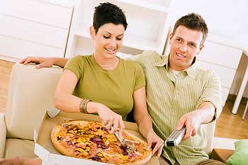 A young man and woman eating pizza while watching television