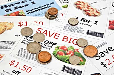 several store and manufacturer coupons in a scattered pile. Coins are littered over the pile
