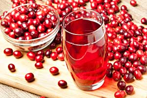 cranberry fruits and a glass of cranberry juice