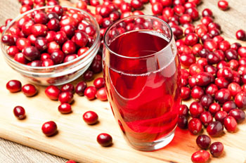 A glass of cranberry juice surrounded by fresh cranberries