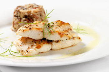 two cooked filets of cod garnished with sprigs of dill