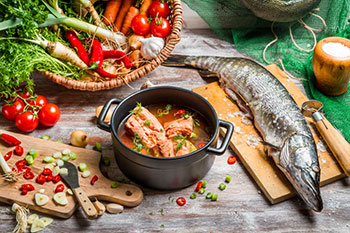 ingredients for a soup containing several elements of a Mediterranean Diet: fish, vegetables, tomatoes (fruits), whole grains