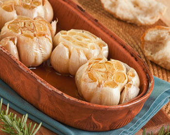 several heads of roasted garlic in a garlic roaster