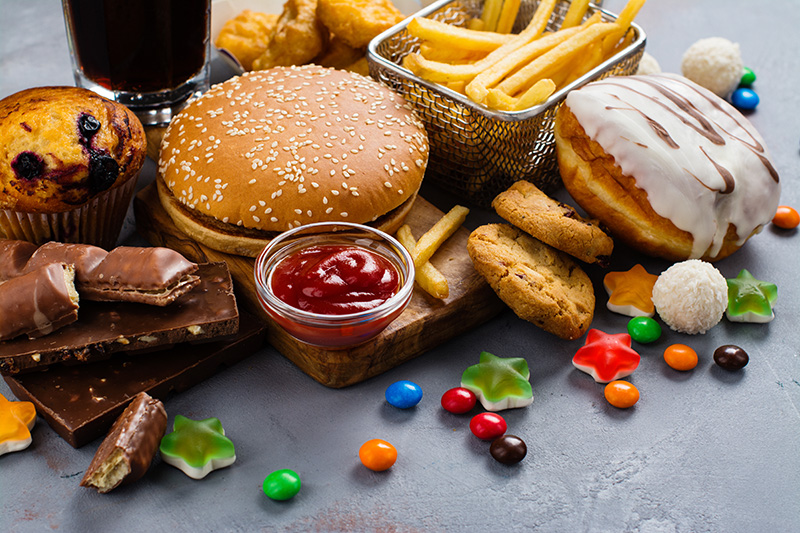 junk food, including a fast food burger, fries, sugary cola, pastries made with refined flours and sugar, candies, and chocolate