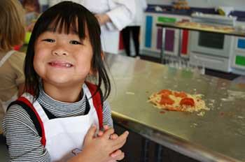 An Asian child smiling at her role in making pizza in a professional kitchen