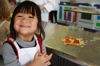 a child with long dark hair stands proudly next to the pizza she made in cooking class