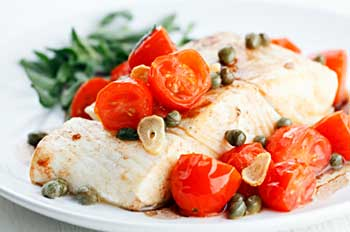 Healthy meal of halibut with tomato, caper, and garlic sauce