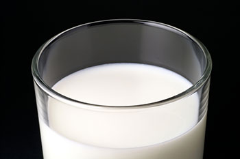 a glass of milk in a clear glass against a dark background