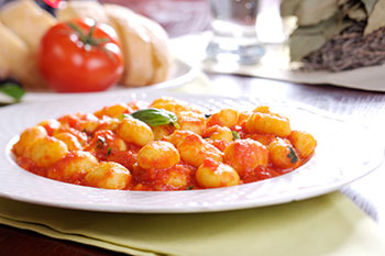a plate of gnocchi with tomato sauce
