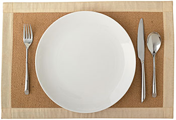 a standard place setting of fork, knife, spoon, and plain, rimless white plate on a placemat