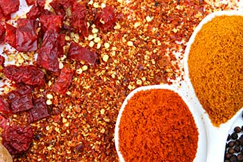 a variety of spices spilled on a flat surface in a decorative manner