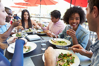 a group of young people dining outdoors at a restaurant