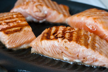 salmon filets roasting on a grill pan