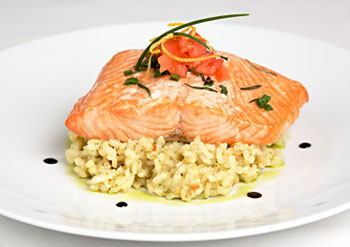 roasted salmon placed on top of a lemon basil risotto, with sauce dotted around the edge of the plate